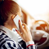 buiness woman talking on phone while driving