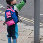 a little boy pushing crosswalk button