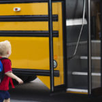 Little boy getting on school bus