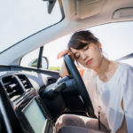 young female driver sleeping in vehicle