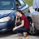Lady that is on the phone trying to figure out who is liable for damages in a car crash pictured