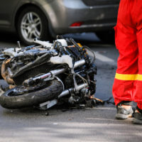 Crashed motorcycle after road accident with a car