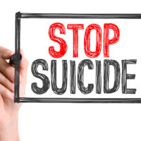 Hand with marker writing the word Stop Suicide