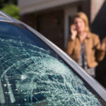 Woman calling For Help After finding broken car windshield