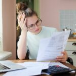 Indoor shot of young European Caucasian girl looking at financial documents at home with deeply bored face looking sick and tired of her economic problems, trying to check counts and all details